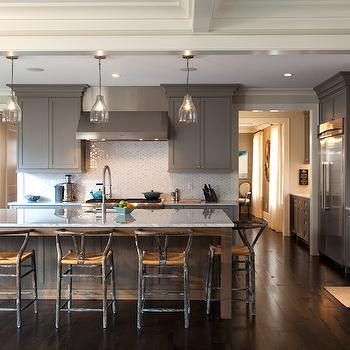 Beautiful gray kitchen with shaker cabinets accented with nickel pulls and light ...
