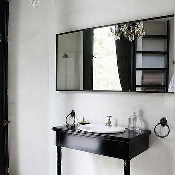 Lonny Magazine - bathrooms - black and white bathroom, 2 leg washstand, repurposed vanity, repurposed sink vanity, repurposed washstand, oval vanity sink, iron towel rings, black framed mirror, plastered walls, bathroom chandelier, diamond pattern floor,