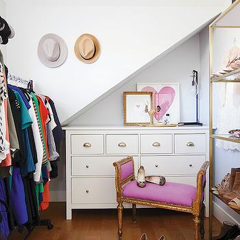 Jillian Harris - closets - white dresser, white dresser with gold hardware, gold cup pull hardware, gold cup pulls, sloped ceiling, sloped closet ceiling, walk in closet, walk in wardrobe, antique bench, antique bench with pink upholstery, antique pink bench, hardwood floors, gold shoe shelves, gold shoe shelf, shoe display, shoe storage, shoe shelving, freestanding clothes rack, heart art, heart art print, leaning art, clothes rack, french bench, sloped ceiling bench, pink french bench, closet bench, brass shoe shelves, brass shelf for shoes,