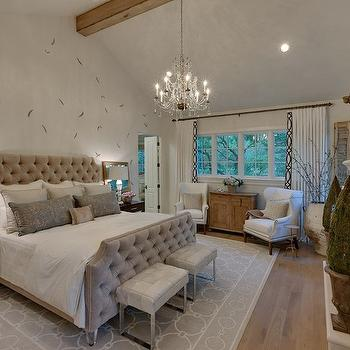 Houston Culture Map - bedrooms - gray button tufted bed, gray pintuck upholstered bed, gray pink tuck headboard, gray velvet tufted headboard, tufted headboard, tufted footboard, benches at end of bed, benches at foot of bed, gray geometric rug, gray chain link rug, chrome based bench, white wingback chair, white wingback chair with nailhead trim, weathered oak cabinet, white drapes, white curtains, white curtains with black geometric trim, black geometric curtain trim, vaulted ceilings, cathedral ceilings, crystal chandelier, feather accent wall, feathered wall treatment, white bedding, white bed linens, gray pillow, contemporary nightstand, coffee stained nightstand, x sided nightstand, matching nightstands, white table lamp, white lamp with gray shade, mirror behind nightstand, mirror on nightstand, bedroom seating, plastered walls, plastered ceiling, plastered wall treatment, gray plastered walls, antique olive jar, olive jar, gray velvet bed, bedroom fireplace,