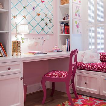 girl's rooms - pink walls, pink wall color, pink girls room, built in desk, built in kids desk, built in desk with bookcase, built in window seat, storage window seat, pink velvet bench cushion, fuchsia pink chair, fuchsia pink desk chair, floral rug, multi colored floral rug, nickel pulls, memo board, ribbon trimmed memo board, plantation shutters, monogrammed pillow, monogrammed ruffle pillow, kids desk, kids built in desk, built in kids desk, kids window seat, kids bookcase, fuchsia  chair,
