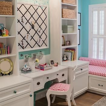 girl's rooms - turquoise walls, turquoise wall color, hardwood floors, built in bookcases, built in shelves, built in desk, built in cabinets with shelves, built in workstation, bow front desk, white bow front desk, kids room desk, girls room desk, white desk chair, black ribbon trimmed memo board, ribbon trimmed pin board, white and turquoise chandelier, white chandelier with turquoise beads, pink geometric seat cushion, built in window seat, pink and white geometric pillow, storage window seat, plantation shutters, beige and black dot rug, black and beige dotted rug, seagrass basket, kids desk, kids bookcases, kids memo boards, kids pin boards, desk chandelier, kids desk chandelier, kids window seat, turquoise and pink kids room,
