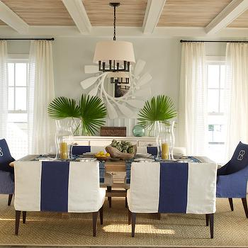 Phoebe Howard - dining rooms - sisal rug, bound sisal rug, beach dining room, nautical dining room, beach dining room, wood paneled ceiling, wood planked ceiling, white beams, white ceiling beams, glass hurricanes, glass candle hurricanes, extra wide dining chair, double wide dining chair, two person dining bench, navy and white slipcovered dining bench, striped dining bench, slipcovered dining bench, trestle dining table, host chairs, slipcovered host chairs, navy blue slipcovered dining chair, monogrammed dining chair, monogrammed host chair, seafoam green walls, seafoam green wall color, board and batten half wall, board and batten trim, ivory sheers, floor length sheers, white sheers, oar mirror, round oar mirror, white oar mirror, white buffet, wooden trinket box, palm fronds, fishermans float, oil rubbed bronze chandelier, oil rubbed bronze drum chandelier, drum pendant light, oil rubbed bronze drum pendant, coastal dining room,