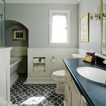 FGY Architects - bathrooms - gray walls, gray wall color, wainscoting, wainscoting half wall, wainscoting paneled bathroom wall, pedestal tub, pedestal bath, arched alcove, gilt framed art, recessed towel storage, recessed bathroom shelves, toilet, small bathroom window, geometric marble tiled floor, geometric gray and white marble floor tile, laser cut marble tile, gray and white laser cut marble, laser cut marble floor tile, off white sink vanity, off white bathroom vanity, black counter, black stone counter, black stone countertop, oval porcelain sink, gilt vanity mirror, gold vanity mirror, gilt crystal sconce, crystal bathroom sconce, crystal hardware, crystal cabinet pull, wainscoting bathroom, bathroom wainscoting, new ravenna tiles, towel niche, towel nook, bathroom nook, bathroom alcove,