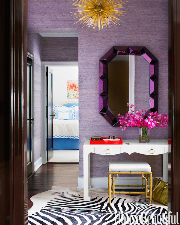 House Beautiful - entrances/foyers - Bungalow 5 Romano Wall Mirror, Juicy Jute Grasscloth, Bungalow 5 Jacqui Desk, Bungalow 5 Collette Stool, Arteriors Zanadoo Chandelier, purple grasscloth wallpaper, purple wallpaper, wallpapered hallway, grasscloth wallpaper, textured wallpaper, purple hallway, purple mirror, geometric purple mirror, metallic purple mirror, modern white desk, contemporary white desk, white desk with ring pull hardware, white lacquered desk, desk console table, gold bamboo stool, faux gold bamboo stool, pink flowers, fresh cut flowers, lacquered orange tray, faux zebra hide, faux zebra hide rug, brass starburst pendant, brass starburst chandelier, purple grasscloth, gold stool, faux bamboo stool, gold urchin chandelier,