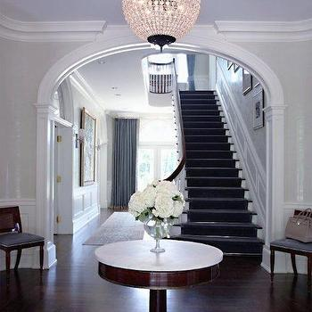 S B Long Interiors - entrances/foyers - crown molding, foyer table, pedestal foyer table, marble topped pedestal table, entry table, footed glass vase, pedestal vase, white hydrangeas, parquet floors, starburst parquet floors, archway, foyer archway, grand staircase, entry seating, gray stair runner, french doors, transom window, blue ceiling, painted blue ceiling, round crystal chandelier, sphere shaped crystal chandelier, large entryway, traditional entryway, foyer table, round foyer table, starburst floor, sunburst floor, arched doorway,