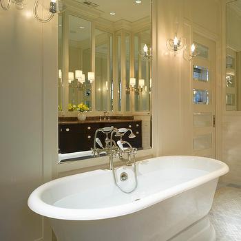Michael A Menn - bathrooms - mirror paneled door, mirror paneled bathroom door, cream wainscoting, bathroom wainscoting, traditional bathroom, mirror framed by wainscoting, bathroom mirror, mirror over bath, mirror behind bath, mirror over tub, mirror above bathtub, crystal wall sconce, crystal bathroom sconce, pedestal tub, pedestal bathtub, freestanding bath, freestanding tub, marble herringbone tile, marble herringbone tiled floors,