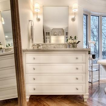 Veranda Interiors - bathrooms - herringbone hardwood floors, wide plank herringbone hardwood floors, leaning floor mirror, bathroom leaning floor mirror, white dresser vanity, dresser style vanity, dresser style sink vanity, white footed dresser vanity, dresser style bathroom vanity, nickel pulls, footed vanity, white dresser bathroom vanity, gray marble, gray marble counter, gray marble countertop, polished nickel wall sconce, contemporary polished nickel wall sconce, floating frame mirror, floating frame vanity mirror, crown molding, bathroom crown molding, hardware herringbone floor, large scale herringbone floor, bathroom floor mirror, restoration hardware floor mirror, dresser style vanity, dresser style washstand, dresser like vanity, dresser like washstand,