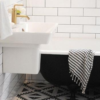 Capree Kimball - bathrooms - black and white floor tile, graphic black and white floor tile, geometric black and white floor tile, black and white cement tile, black and white bathroom floors, black and white bathroom, black tub, black bath, black bathtub, black claw foot tub, black claw foot bath, fouta towel, striped fouta towel, moroccan hand towel, linear white subway tile, linear white tile, white tile with black grout, black grout, dark grout, wall mount sink, modern wall mount sink, contemporary wall mounted sink, gold faucet, modern gold faucet, brushed gold faucet, wall mounted sink, brushed gold faucet, kohler faucet, kohler brushed goldfaucet, Kohler Reve Sink, Kohler Brushed Gold Purist Faucet,