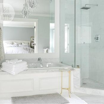 Style at Home - bathrooms - bathtub wainscoting, tub wainscoting, wainscoting bathtub, drop in bathtub, marble tub surround, bathtub mirror, ceiling height mirror, bathroom table, brass accent table, marble top accent table, corner shower, seamless glass shower, marble shower surround, white marble shower tiles, corner shower ideas, mosaic marble floor, rain shower head,