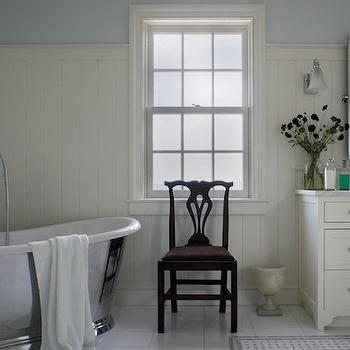 Christopher Burns Interiors - bathrooms - beadboard walls, beadboard bathroom walls, beadboard paneling, bathroom beadboard, blue walls, blue wall color, white and blue bathroom, sash window, chippendale chair, silver tub, silver bathtub, freestanding bath, freestanding bath in corner, freestanding tub in corner, floor mount faucet, floor mount faucet with shower head, white floor tile, white tiled floors, marble basketweave tile, marble basketweave tiled rug, white vanity, white sink vanity, built in white vanity, shaker front sink vanity, nickel pulls, marble counters, marble countertop, gooseneck faucet, towel ring, nickel sconce with frosted shade, pivot vanity mirror, rectangular pivot mirror, corner freestanding tub, corner freestanding bathtub, bathroom beadboard, cream beadboard, cream and blue bathrooms,