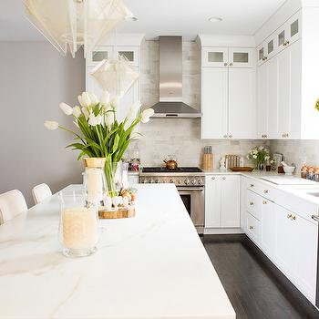 Refinery 29 - kitchens - long island, long kitchen island, endless island, endless kitchen island, shaker cabinets, white shaker cabinets, brass hardware, brass cabinet hardware, brass kitchen hardware, brass kitchen cabinet hardware, ceiling height cabinets, ceiling height kitchen cabinets, glass front kitchen cabinets, white marble countertops, marble subway tiles, marble subway tile backsplash, topiary, kitchen topiary, ivory barstools, modern light pendants, double door refrigerator,