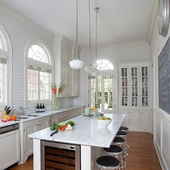 Ty Larkins Interiors - kitchens - ivory cabinets, ivory kitchen cabinets, white marble countertops, subway tiles, subway tile backsplash, ceiling height subway tiles, ceiling height backsplash, ceiling height backsplash tiles, arched windows, arched kitchen windows, arched transom window, transom window, glass front hutch, glass door hutch, built in hutch, kitchen hutch, kitchen chalkboard, kitchen clock, long island, long kitchen island, center island, long center island, countertop overhang, vintage barstools, integrated wine cooler, island wine cooler, kitchen island wine cooler, island wine fridge, kitchen island wine fridge, classic gray, gray paint colors, ivory crown moldings,