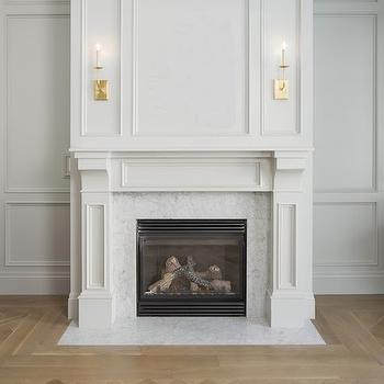 White & Gold Design - living rooms - living room wainscoting, gray wainscoting, light gray wainscoting, pale gray wainscoting, full wall wainscoting, raised front wainscoting, raised panel wainscoting, wainscoting paneled fireplace, fireplace wainscoting, marble fireplace surround, marble fireplace hearth, brass wall sconce, brass candelabra wall sconce, sconces over fireplace, antique brass wall sconce, herringbone hardwood floors, fireplace trim, fireplace moldings, gray fireplace, gray fireplace mantle, fireplace sconces,