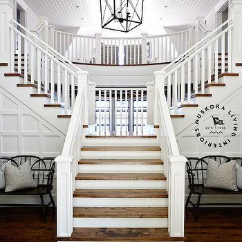 Muskoka Living - entrances/foyers - double staircase, double sided staircase, double sided stairway, grand staircase, grand entrance, white spindles, white banister, stained stair treads, elegant stairway, elegant staircase, hardwood floors, black antique bench, antique bench, board and batten, criss cross board and batten, board and batten entryway, board and batten foyer, beadboard ceilings, entryway beadboard ceilings, foyer beadboard ceilings, lantern pendant, iron lantern pendant, foyer lantern pendant, staircase lantern pendant,