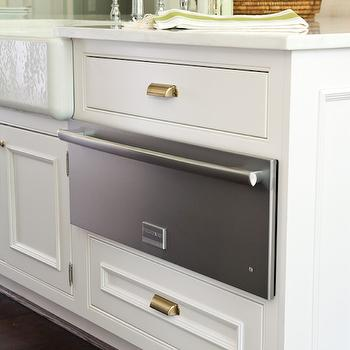 White kitchen island is accented with brass pulls topped with white marble framing ...