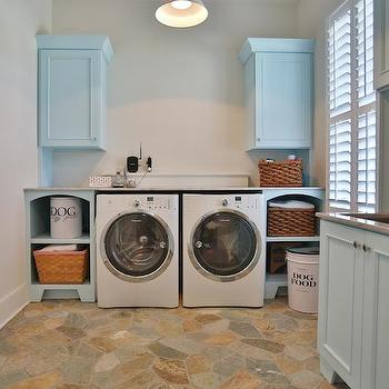 Stacye Love - laundry/mud rooms - baby blue cabinets, blue laundry room cabinets, baby blue laundry room cabinets, nickel cabinet pulls, marble counters, spray faucet, spray head faucet, stainless steel utility sink, laundry room sink, flagstone floors, flagstone laundry room floors, stone floor tile, front load washer, front load dryer, white front load washer, white front load dryer, open laundry room cabinets, woven basket, enamel dog food bin, white enamel dog food storage, enamel pendant, beveled subway tile, beveled subway tile backsplash, shutters, laundry room window shutters, blue cabinets, blue laundry room cabinets, painted laundry room cabinets, laundry room shelves, flagstone tiles,