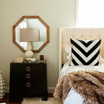 JWS Interiors - bedrooms - bed in front of window, headboard in front of window, gold mirror, mirror over nightstand, over the nightstand mirror, gold octagon mirror, black nightstand, black lacquer nightstand, lacquered nightstand, cream table lamp, linen headboard, tufted headboard, faux fur blanket, chevron pillow, black and white pillow, black and white chevron pillow,
