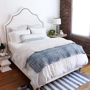 coco & kelley - bedrooms - white arched headboard, arched headboard with nailhead trim, white upholstered headboard, white bed linens, white bedding, blue and white striped rug, exposed brick wall, exposed brick accent wall, exposed brick window wall, modern white accent table, round wood side table, scalloped shade table lamp, table lamp with scalloped shade, mismatched bedside tables, mismatched nightstands, blue tie dye throw, bunny williams throw, sheer window shade, blue striped lumbar pillow, blue and white stripe lumbar pillow, light gray bedding, light gray bed linens, nailhead headboard, studded headboard, white nailhead headboard, bedroom brick wall, bedroom exposed brick wall,