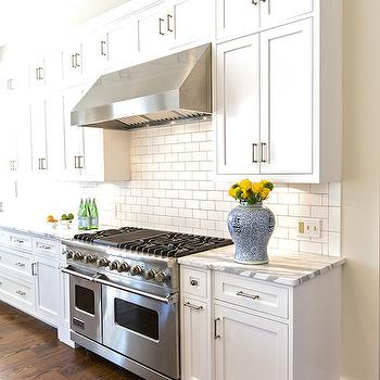 Hallie Henley Design - kitchens - chinese ginger jar, ginger jar, stacked cabinets, stacked kitchen cabinets, stacked upper cabinets, white and gray marble, white marble with gray veining, subway tiles, subway tiled backsplash, stainless steel hood,