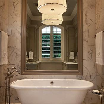 Wolfe Rizor Interiors - bathrooms - floor to ceiling marble tile, large scale marble tile, marble tile, marble floor tile, freestanding pedestal tub, pedestal bathtub, scalloped pendant, scalloped drum pendant, tub filler faucet, floor mount bath faucet, towel bar, monogrammed bath towels, polished aluminum accent table, oversize mirror, mirror over tub, mirror above bath, mirror behind tub, taupe wall mirror, bathtub chandelier, taupe mirror, taupe beveled mirror, bathtub mirror,