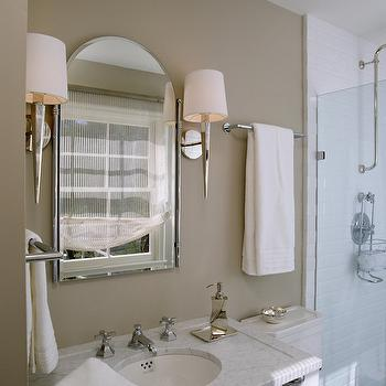 Lonny Magazine - bathrooms: taupe walls, taupe bathroom walls, faceted mirrored sconce, faceted polished nickel sconce, arched beveled mirror, arched vanity mirror, polished nickel towel bar, ivory bath towels, towel bar over toilet, marble topped washstand sink, marble washstand sink, chrome washstand sink, hot and cold faucet, polished nickel soap dispenser, glass shower screen, subway tile, subway tiled shower surround, white and taupe bath, white and taupe bathrooms. mirrored sconces, 2 leg washstand, marble top washstand, shower subway tiles, taupe bathroom walls,