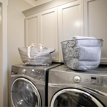 HGTV - laundry/mud rooms - laundry room, pocket door laundry room, laundry room pocket door, cabinets over washer dryer, storage over washer dryer, cream cabinets, laundry room cabinets, silver washer dryer, front load washer dryer,