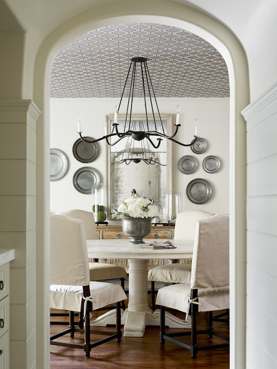 Elle Scrase - dining rooms - decorative wall plates, pewter wall plates, wallpapered ceiling, iron chandelier, beveled mirror, dining room mirror, sideboard, antique sideboard, round dining table, white dining table, white round dining table, camelback dining chairs, slipcovered dining chairs, archway, dining room archway, arched door, arched doorway,