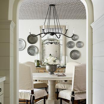 Elle Scrase - dining rooms: decorative wall plates, pewter wall plates, wallpapered ceiling, iron chandelier, beveled mirror, dining room mirror, sideboard, antique sideboard, round dining table, white dining table, white round dining table, camelback dining chairs, slipcovered dining chairs, archway, dining room archway, arched door, arched doorway,
