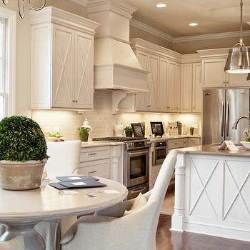 Stunning kitchen with off-white cabinets accented with nickel hardware and white ...