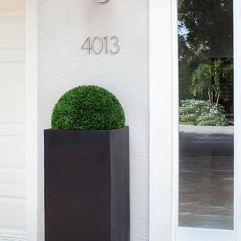 Krista Watterworth Design Studio - home exteriors - red brick porch, gray exterior walls, modern black planter, tall modern black planter, potted boxwood, galvanized steel wall sconce, galvanized barn wall sconce, silver house numbers, modern house numbers, house number ideas, metal house numbers, metal house number ideas,