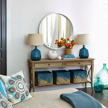 Tracery Interiors - living rooms: round capiz mirror, peacock blue lamps, two drawer console table with shelf, built in table shelf, blue baskets, blue knitted throw, beige sofa, blue pillows, floral pillows, turquoise glass bottles, console table with shelf, ombre baskets, blue woven baskets, peacock blue table lamps, capiz mirror, linen sofa,