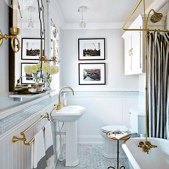 Style at Home - bathrooms - beadboard half wall, beadboard paneled lower wall, brass towel rail, brass towel holder, marble mosaic border, marble mosaic bathroom border, arched antiqued gold mirror, brass candle sconce, slim bathroom shelf, marble herringbone floor tile, iron accent table, gray claw foot tub, gray claw foot bath, claw foot bath with built in shower head, gray and white shower curtain, claw foot tub with integrated shower head, light gray walls, black and white framed photography, bathroom art, pedestal sink, brass gooseneck faucet, cabinets over toilet, toilet cabinetry, iron accent table, brass tub faucet with shower head, vintage style claw foot tub faucet, white gray and brass bathroom, bathroom beadboard, marble shelf, marble bathroom shelf, marble herringbone tiles, striped shower curtain, black and white stripe shower curtain, medicine cabinet over toilet, over the toilet medicine cabinet, above the toilet medicine cabinet,