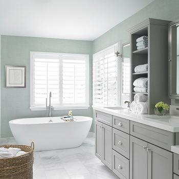 Krista Watterworth Design Studio - bathrooms - gray green grasscloth, gray green grasscloth wallpaper, plantation shutters, bathroom plantation shutters, gray shaker vanity, gray shaker front vanity, polished nickel hardware, shaker sink vanity, bathroom vanity with center cabinet, white quartz counters, dual sink vanity, nickel medicine cabinet, rectangular marble floor tile, marble bathroom floors, oval tub, oval freestanding tub, oval freestanding bathtub, modern tub filler faucet, woven laundry hamper, woven basket with handles, gray and blue bathrooms, gray washstand, gray double vanity, gray double sink vanity, egg shape bathtub, egg shaped bathtub, white marble floor, gray cabinets, gray vanity cabinets, gray bathroom cabinets, gray console cabinet,