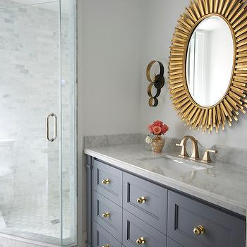 Meredith Heron Design - bathrooms: gray vanity, brass knobs, white marble countertop, oval brass mirror, brass ring sconce, corner shower with linear marble surround, white and gray geometric floor, brass faucet, corner shower, brass bathroom accents, oval mirror, brass mirror, geometric bathroom floor, gray washstand, oval vanity mirror, brass vanity mirror, gold mirror, gold oval mirror, ring sconce, brass ring sconce, gold ring sconce, gray vanity with brass knobs, gray washstand with brass knobs, marble geometric floors, marble geometric tiles, corner shower, corner shower ideas, brass vanity faucet, gray and blue bathroom,