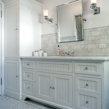 grey bathroom with tall beadboard cabinets beside an extra long vanity