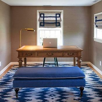 dens/libraries/offices - navy and taupe ikat stripe rug, ikat striped rug, navy and taupe rug, navy blue ottoman, navy ottoman on castors, grasscloth wallpaper, grasscloth office wallpaper, dark grasscloth wallpaper, oak desk, oak desk with turned legs, desk facing into room, greek key trimmed roman shade, greek key roman shade, brass floor lamp, brass bankers floor lamp, light hardwood floors, ikat rug, blue ikat rug, blue bench, greek key roman shades, blue and gray roman shades, taupe grasslcoth,