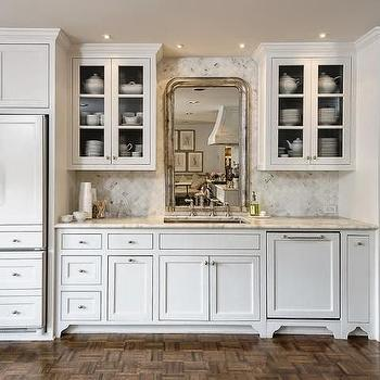 Lisa Luby Ryan - kitchens - inset cabinets, flush front cabinets, cabinet front refrigerator, hidden refrigerator, cabinet paneled refrigerator, white marble counter, gray and white marble counter, diamond laid marble tile backsplash, glass paned cabinets, ceiling height upper cabinets, mirror behind sink, make a small kitchen look bigger, visually expand a small kitchen, cabinet front dishwasher, antique silver leafed mirror, silver leaf mirror, darker painted ceiling, parquet wood floors, parquet hardwood floors, paneled fridge, paneled freezer drawers, concealed fridge, mirrored behind kitchen sink, kitchen sink mirror, french country kitchens, glass door kitchen cabinets, kitchen backsplash ideas, diamond marble backsplash, diamond pattern backsplash, paneled dishwasher, diamond pattern backsplash tiles,