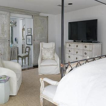 Lisa Luby Ryan - bedrooms: sliding french style doors, distressed gray sliding paneled doors, iron canopy bed, iron and brass canopy bed, french settee, distressed french settee, gray garden stool, swooped arm slipcovered chair, white slipcovered arm chair, bound sisal rug, rug under bed, serpentine front dresser, distressed serpentine front dresser, tv on top of dressed, bedroom tv, sliding bathroom doors, gray and white patterned pillow, white pillow with gray border, french style bedroom, gray french bedroom, french country bedroom ideas, cornice over sliding doors, bathroom doors, sliding bathroom doors, distressed bathroom doors, distressed sliding doors, distressed sliding bathroom doors, swooped arm chairs, bedroom sitting area, serpentine dresser, gray distressed doors, gray sliding doors,
