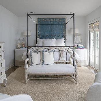 Lisa Luby Ryan - bedrooms - iron canopy bed, iron canopy bed with gothic detail, round skirted nightstands, banded linen skirted nightstand, tall french table lamp, french country style bedroom, peacock blue antique wall panel, teal blue antique wall panel, antique wall panel headboard, french doors, bedroom french doors, ivory roman shade, french settee bench, distressed french settee, blue embroidered border pillow, sisal rug, rug under bed, rug below bed, serpentine dresser, distressed gray serpentine dresser, tv on dresser, tv atop dresser, gothic bed, gothic canopy bed, gothic iron bed, gothic iron canopy bed, skirted nightstands, banded nightstands, banded skirted nightstands, art behind bed, bed art panel,