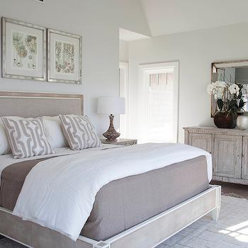 Milton Development - bedrooms: gray fringed rug, rug under bed, bed on rug, mirror front nightstand, mirrored circle nightstand, mottled gray table lamp, mottled glass table lamp, mirror framed art, mirror framed abstract art, art over headboard, faux shagreen bed, gray faux shagreen bed, upholstered gray bed, gray bed linens, folded duvet, gray geometric pillow, gray chain link pillow, distressed gray chest, beveled antique mirror, gray wing back chair, gray floor lamp, neutral palette bedroom, gray walls, white and gray bedrooms, mirrored nightstands, gray mirrored nightstands, art over bed, over the bed art, above the bed art, gray bed, white and grey bedding, square beveled mirror, gray wash chest,