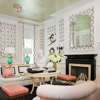 Tobi Fairley - living rooms: black and white wallpaper, geometric wallpaper, wallpaper accent panels, wallpapered wainscoting panels, arched beveled mirror, embroidery trimmed drapes, white drapes with geometric trim, blush pink silk pillow, pink silk pillow, gold x bench stool, gold stool with pink seat, round ivory accent table, rolled back arm chair, black lacquered fireplace, glossy black fireplace, black lacquered wall sconce, white armless sofa, white sofa with black grosgrain trim, armless sofa, emerald green glass lamp, emerald green fluted glass lamp, gold leafed ceiling, gold leaf ceiling, pink beaded flush mount chandelier, bust, stacked books, black and white abstract art, black and white living room, black and white geometric wallpaper, wallpapered art panels, living room wainscoting, black and white sofa, black and white curtains, armless sofa, black and white armless sofa, salmon pink pillows, salmon pink stools, gold cieling,