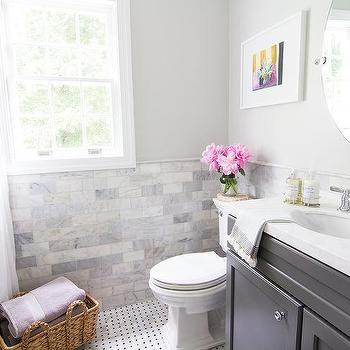 Curbly - bathrooms: quartz that looks like marble, marble counter alternatives, oval vanity sink, polished chrome faucet, kohler faucets, beveled oval mirror, oval pivot mirror, marble subway tile, venatino marble tile, venatino polished marble tile, marble tiled wainscoting, black pom pom trimmed shower curtain, pom pom shower curtain, marble basketweave floor tile, marble basketweave with black dot, dark gray bathroom vanity, gray sink vanity, art over toilet, still life art, sash bathroom window, small bathroom ideas, gray bathroom, white and gray bathroom design, marble chair rail, charcoal gray washstand, charcoal gray vanity, aspen quartz, aspen quartz counter, apsen quartz countertop, venatino marble, venatino marble backsplash, marble like countertops, white marble like countertops, white marble alternatives, kraftmaid vanity, kraftmaid sink vanity, kraftmaid washstand, gray kraftmaid vanity, gray kraftmaid washstand, marble wainscoting, marble bathroom wainscoting, venatino subway tiles, venatino marble subway tiles, shower curtain with pom pom trim, white marble substitutes,
