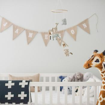 Style Me Pretty - nurseries - name garland, bunting name garland, nursery garlands, neutral nursery, baby animal nursery mobile, safari animal nursery mobile, large giraffe stuffed toy, white crib, black and white cross throw, black and white cross print throw, decor over crib, wall art over crib, decorating over crib, nursery mobile, nursery garland, garland over crib, over the crib garland, above the crib garland,