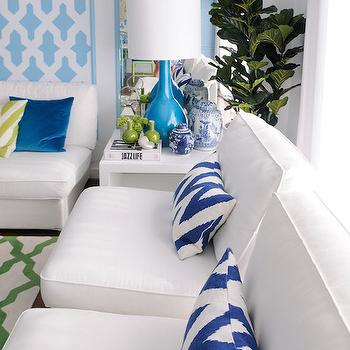 Maria Barros - living rooms - green and blue living room design, white slipper chair, armless white slipper chair, navy chevron lumbar pillow, navy blue chevron pillow, modern white side table, modern white end table, turquoise blue bottle lamp, fiddle leaf fig plant, turquoise trimmed mirror, panels of wall stenciling, moroccan tile wall stencil, turquoise moroccan tile wall stencil, stenciled wall panel, armless white sofa, green and white moroccan tile rug, tropical living room ideas, blue trellis stencil, blue mirror, blue framed mirror, mirror over end tables, slipper chairs, navy chevron pillow, navy chevron lumbar pillow, turquoise bottle lamp,