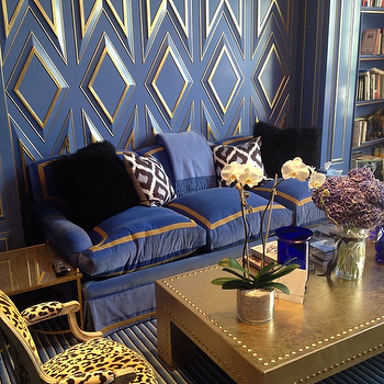 Kirsten Kelli - living rooms - blue living rooms, blue and gold living rooms, blue and gold walls, gold trim, gold geometric trim, gold wall trim, blue sofa, blue velvet sofa, blue and gold sofa, roll arm sofa, blue roll arm sofa, blue skirted sofa, black sheepskin pillows, gold coffee table, studded coffee table, gold studded coffee table, chunky coffee table, blue striped rug, leopard chair, french leopard chair, gold end tables, blue built ins, blue built in cabinets,