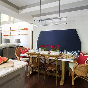 At Home in Arkansas - kitchens - eat in kitchen, nautical kitchen, navy blue upholstered banquette, upholstered banquette, navy banquette with nailhead trim, trestle dining table, trestle dining table with steel top, stainless steel topped trestle table, rattan dining chair, rattan armchair, red pillow with white grosgrain trim, nautical red pillow, french cafe chair, x back bentwood chair, linear nickel pendant light, linear lantern pendant light, tray ceiling, tray ceiling with painted border, beachy kitchen, red white and blue kitchen, red white and blue dining room, lake house dining room, lake house breakfast room, navy banquette, nailhead banquette, stainless steel top dining table, stainless steel dining table, steel and wood dining table, wicker dining chairs, linear light pendant, painted tray ceiling,