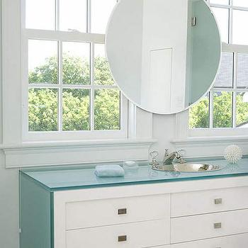 Brooks & Falotico - bathrooms - crystal faucet, rectangular nickel cabinet pulls, brushed nickel cabinet pulls, tempered glass counter, glass countertop, glass vanity counter, glass waterfall edge counter, round hammered nickel sink, round silver sink, dresser like vanity, bathroom vanity with drawers, contemporary white bathroom vanity, round beveled mirror, round vanity mirror, mirror over windows, mirror in front of windows, double sash windows, mirror over bathroom window, contemporary bathroom, waterfall vanity, waterfall edge countertop, waterfall make up vanity,