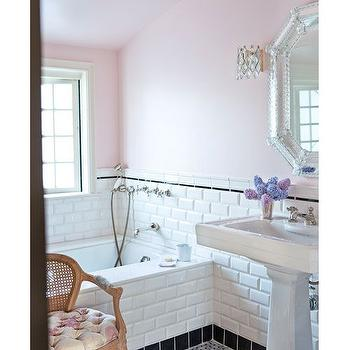 Ruthie Chapman Sommers - bathrooms - sloped bathroom ceilings, pink black and white bathroom, feminine bathrooms, pink bathroom walls, powder pink walls, beveled subway tile, white beveled subway tile, tiled bathroom wainscoting, tiled drop in tub surround, black tile baseboard, black pencil tile, pencil tile border, rectangular pedestal sink, octagonal venetian mirror, crystal beaded wall sconce, window over tub, wall mount faucet, wall mount shower head, vintage cane back chair, tufted chair with cane back, basketweave tiled floors, marble basketweave tile, bathroom sloped ceiling, pink bathrooms, white and pink bathrooms, pink and black bathrooms, bathroom with subway tiles, black baseboards, venetian vanity mirror, octagon vanity mirror, subway tiled bathroom, bathroom char, cane chair,