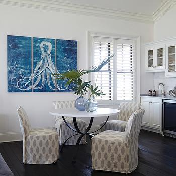 Tracery Interiors - dining rooms - octopus triptych, octopus art, octopus triptych art, black and white dining table, round dining table, ikat dining chairs, slipcovered dining chairs, dining room art, dark wood floors, kitchenette, chicken wire cabinets, beverage fridge, living room kitchenette,